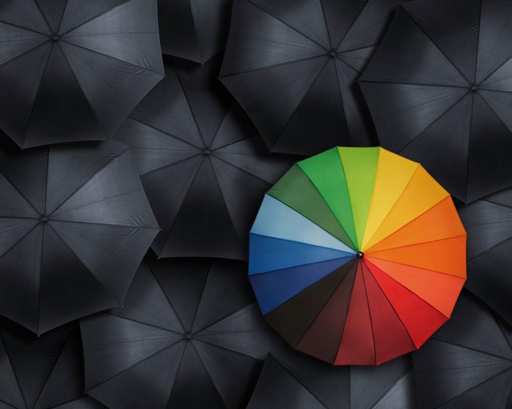 One multi-coloured umbrella in a sea of black umbrellas
