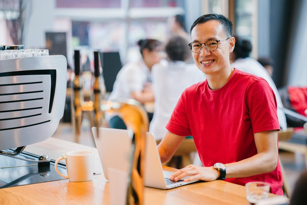 Man wearing red t-shirt, smiling at camera while using a laptop in a cafe