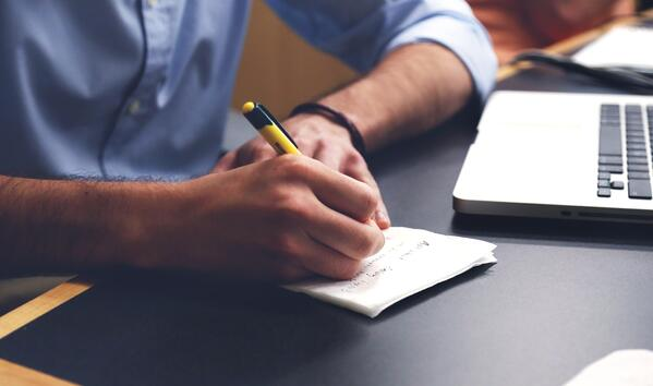Man writing notes with a pen and paper