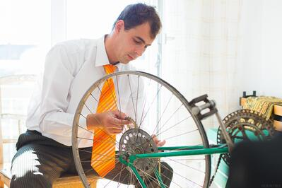 Man in business attire repairing a bike