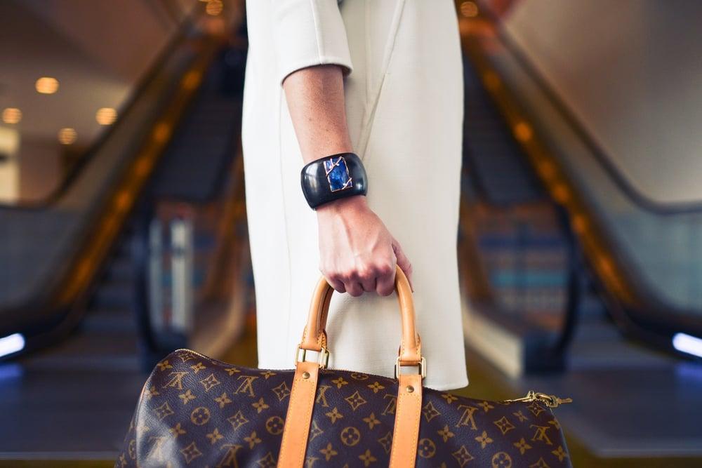 Woman's hand holding a Louis Vuitton bag