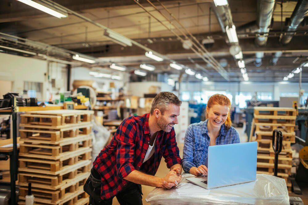 Man and woman working on laptop in factory