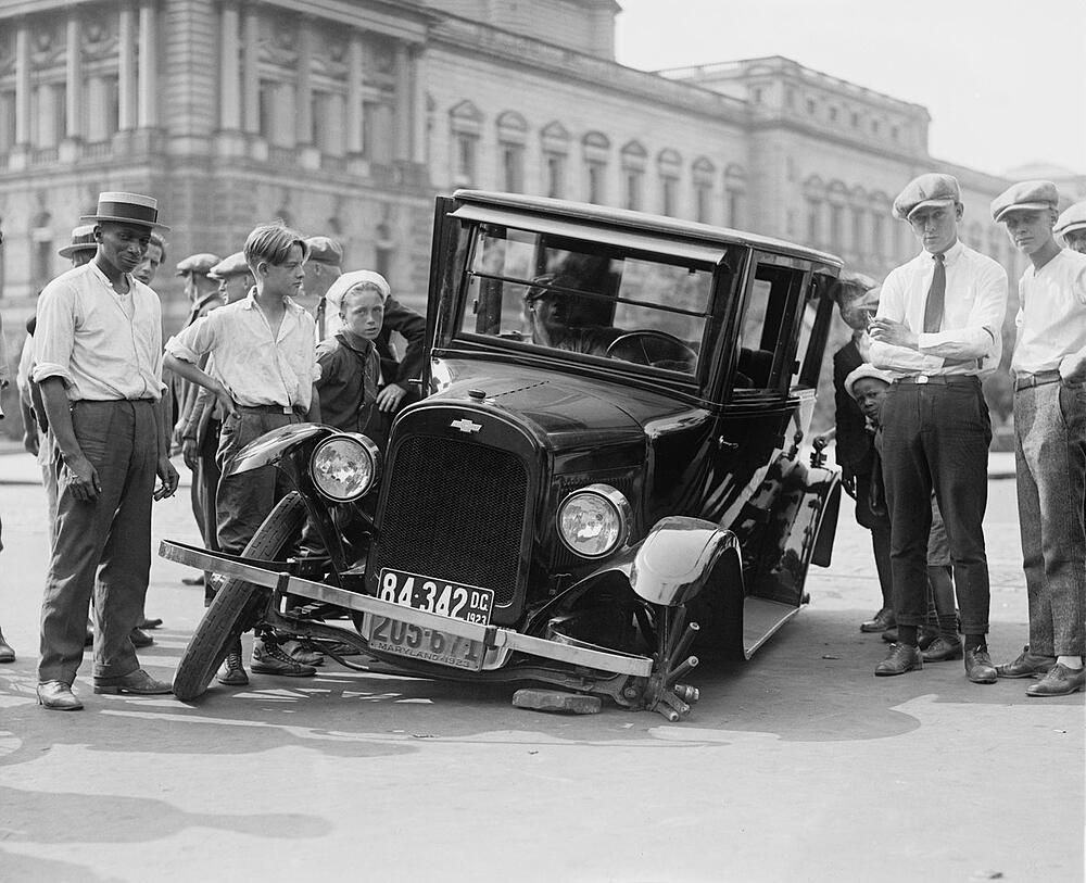 Photo from 1920s of men and boys standing around car with front wheel broken off