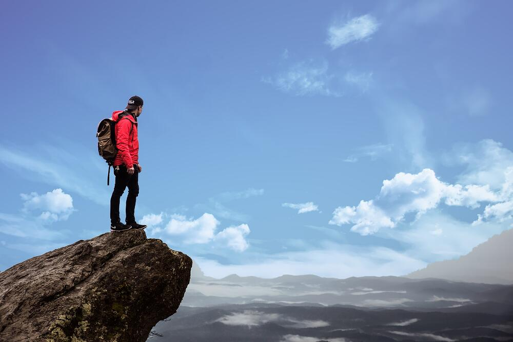 Mountain climber looking into distance on edge of rock