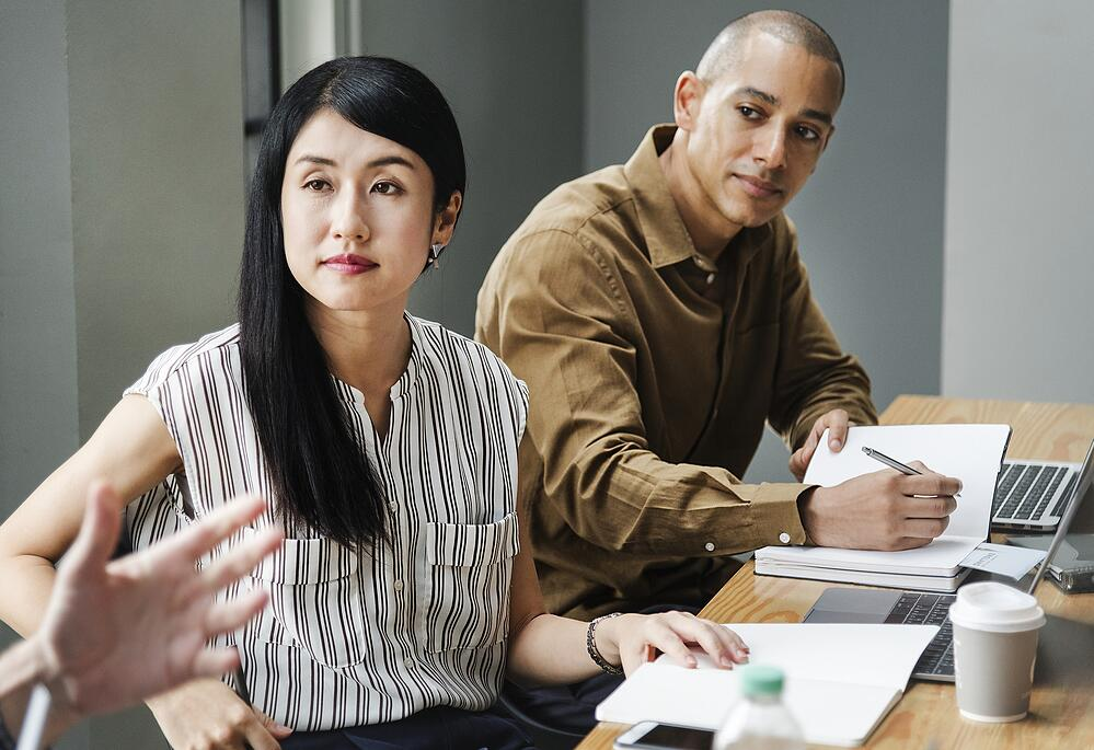 Young woman and man listening to someone speak during business meeting