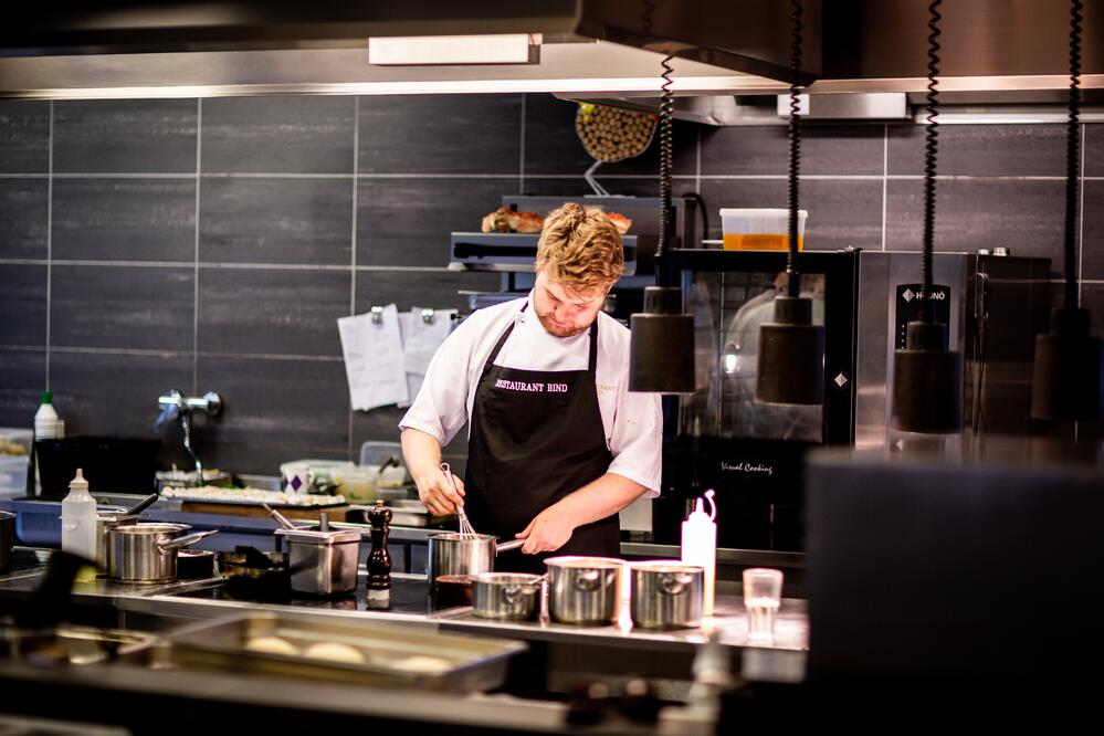 Man in chef's apron working in bar kitchen