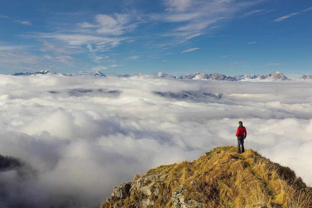 Hiker on a mountain looking down at clouds
