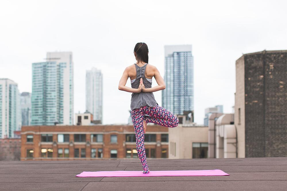 Back view of woman balancing on one foot while doing yoga