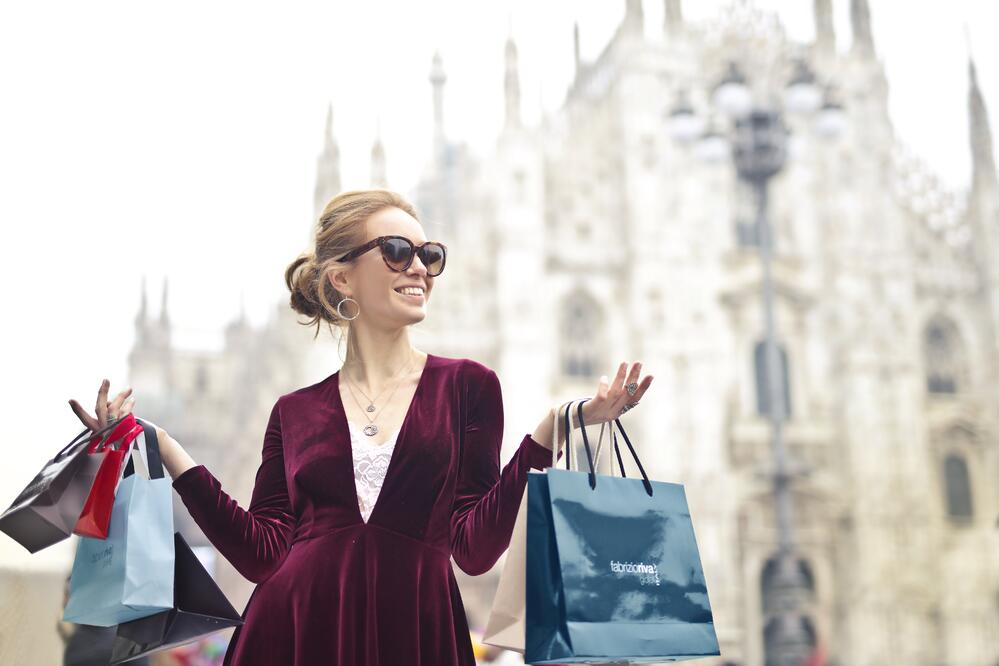 Beautiful woman holding shopping bags with cathedral in background