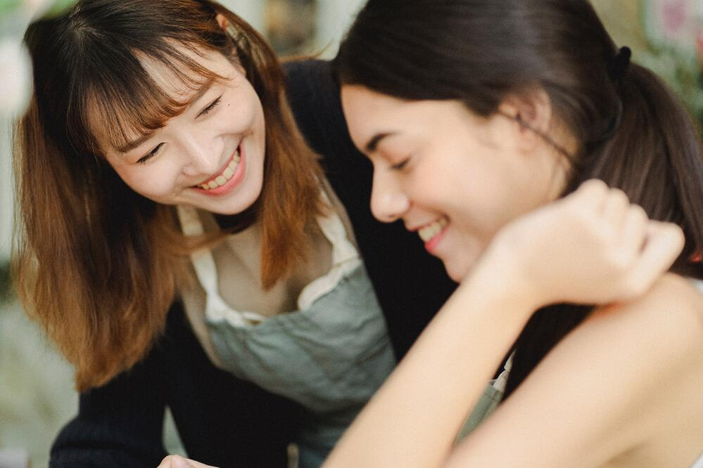 Woman wearing work apron smiling at younger woman
