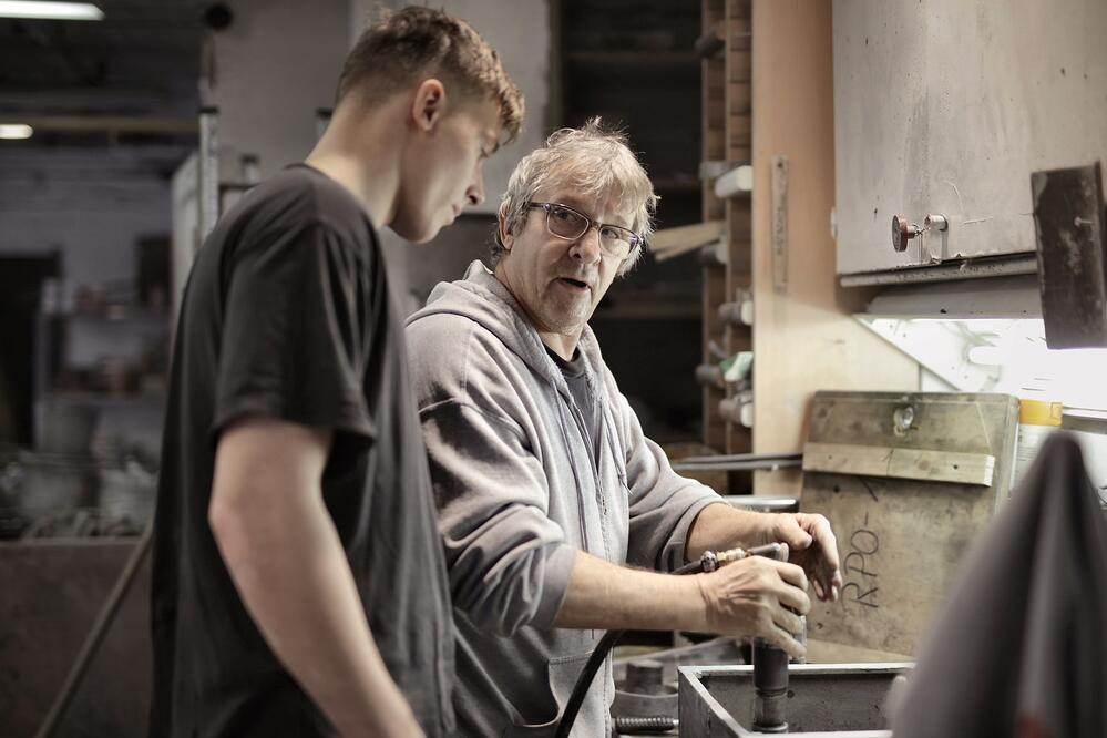 Young man and older man in workshop