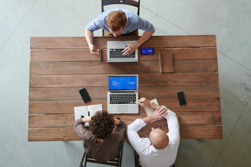 Three people at business meeting photographed from above