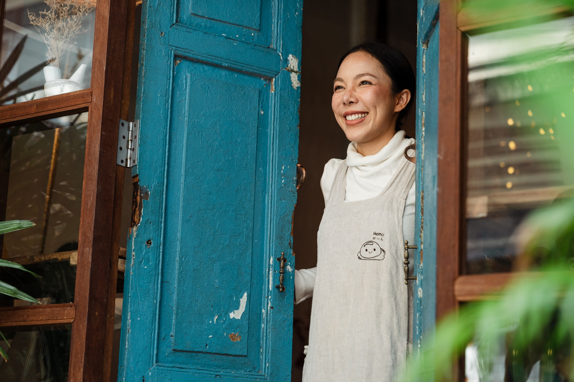 Small business owner standing in her doorway