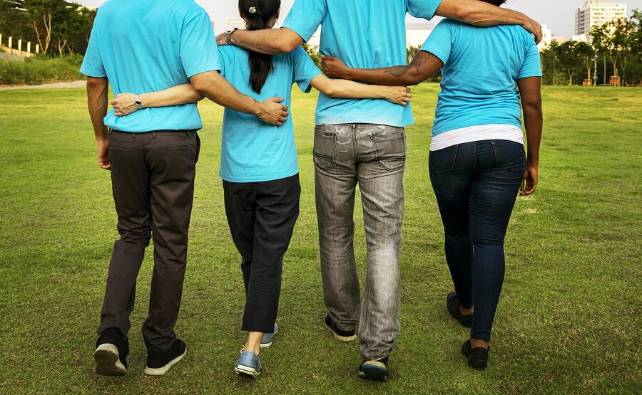 Two men and two women wearing bright blue t-shirts while walking with their arms around each other. Photographed from behind.