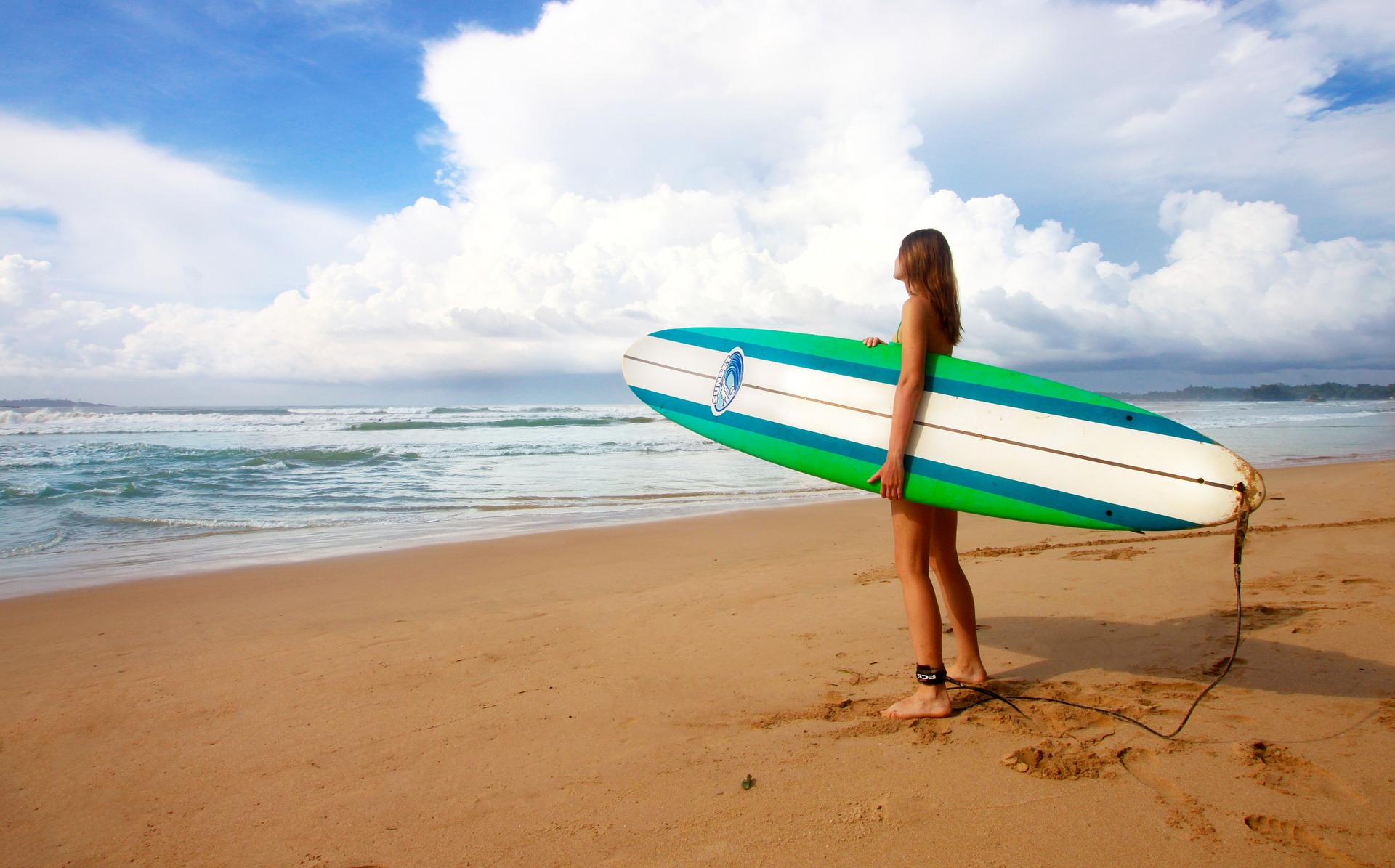 Female surfer standing on beach holding long board