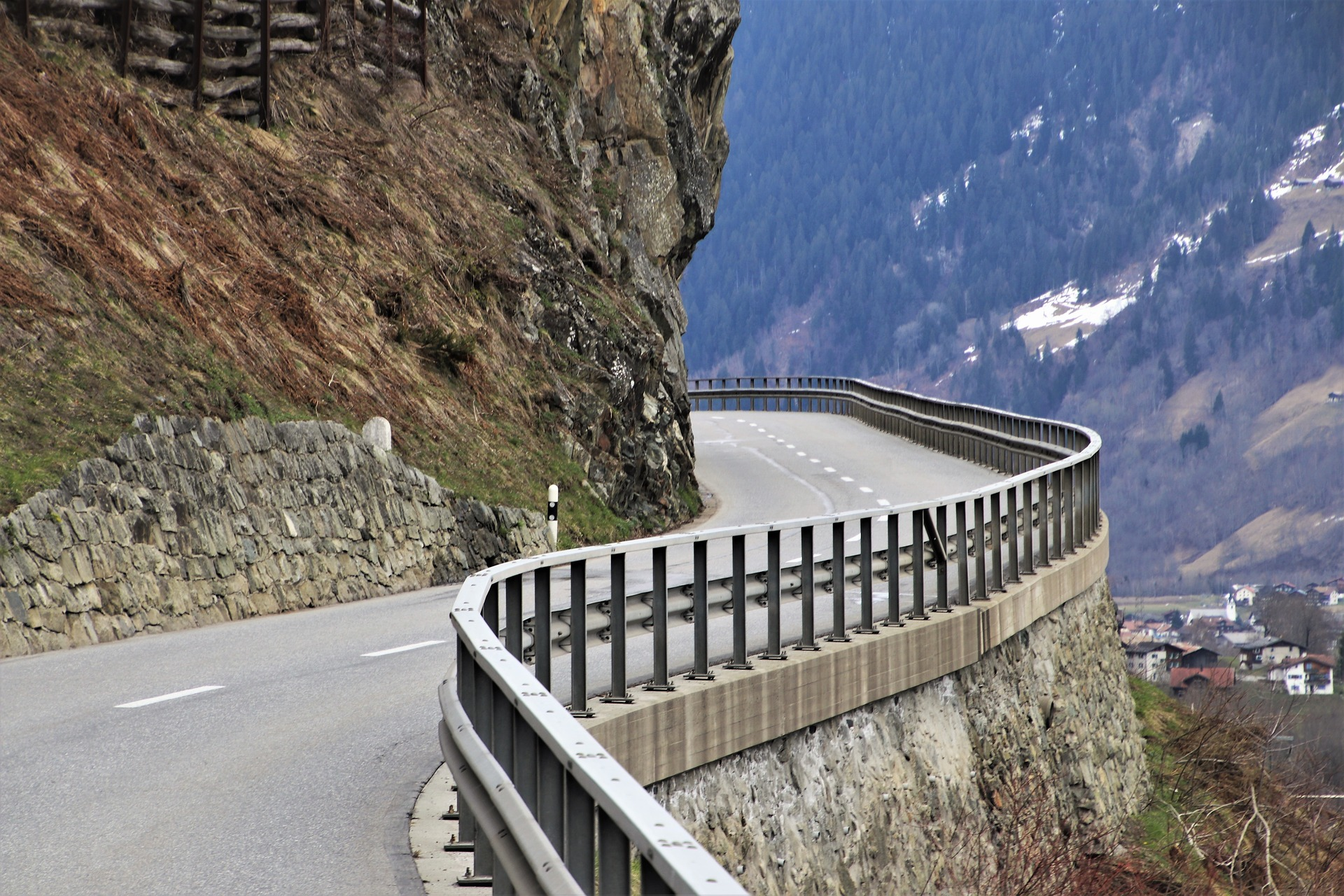 Picture of road winding around a mountain in the Alps