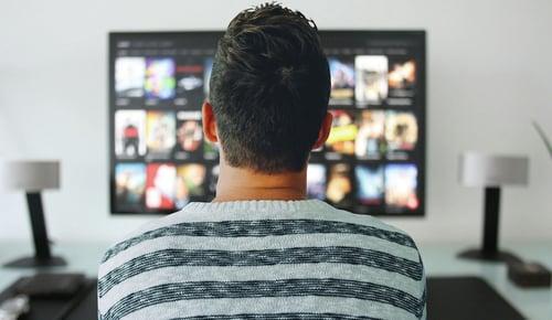 Photo taken from behind of man watching TV