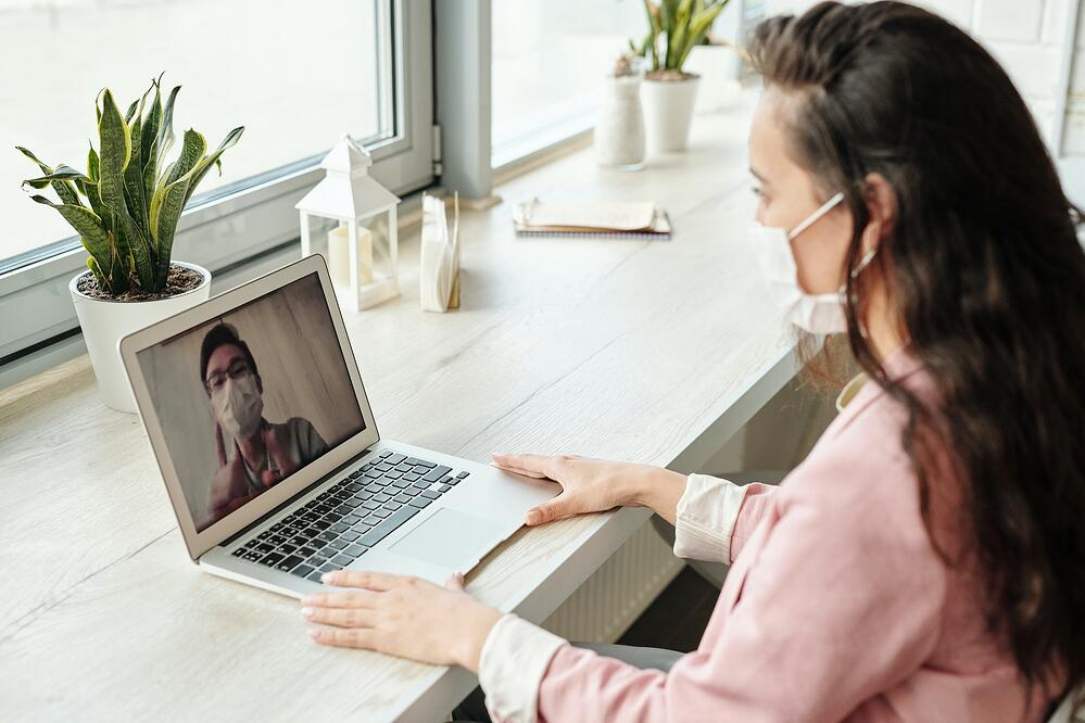 Woman and man having a video call while wearing face masks